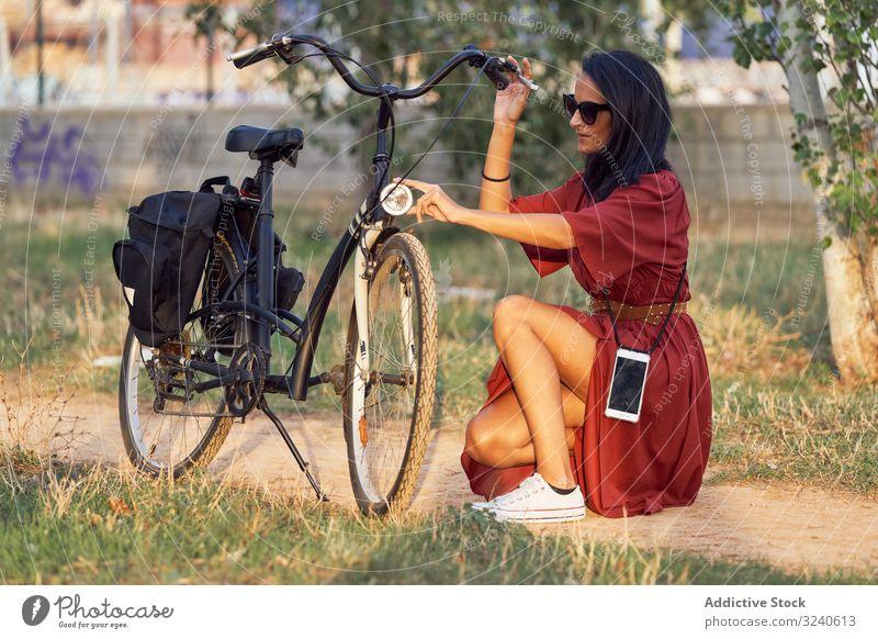 Frau repariert Fahrrad im Park fixieren Scheinwerfer Weg lässig Großstadt Sommer Aktivität Fahrzeug Reparatur ausrichten Verkehr Lifestyle ruhen