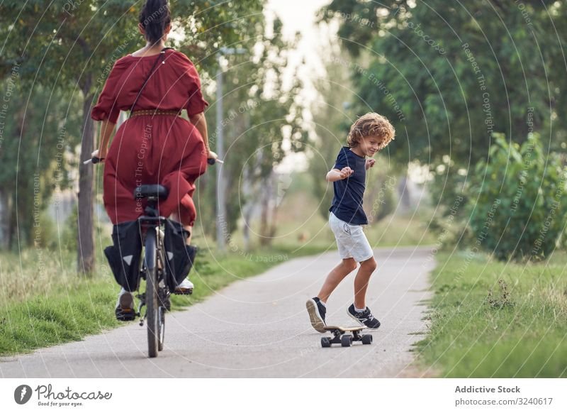 Mutter und Sohn reiten entlang des Parkwegs Mitfahrgelegenheit Weg Skateboard Fahrrad Zusammensein Spaß Familie Glück Junge Frau Kind Sommer Freude froh