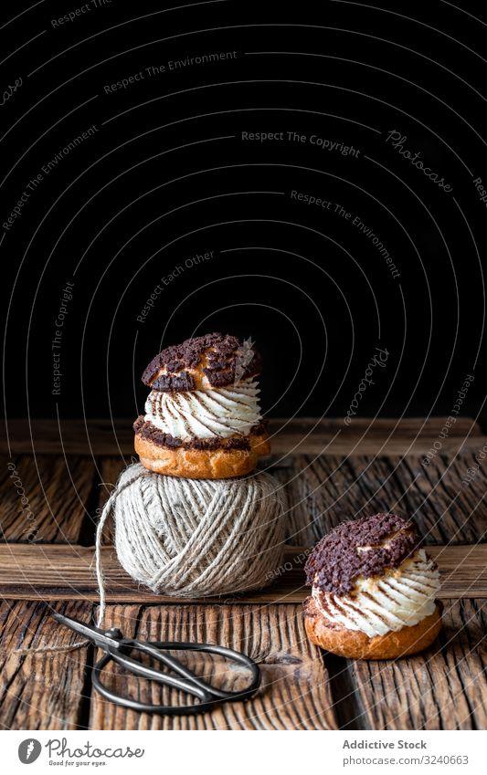 Köstliche Brandteigbrötchen und Wollfäden auf Holztisch choux Sahne Gebäck Dessert Lebensmittel Profiterole Faser Ball Garn Schere selbstgemacht lecker gebacken