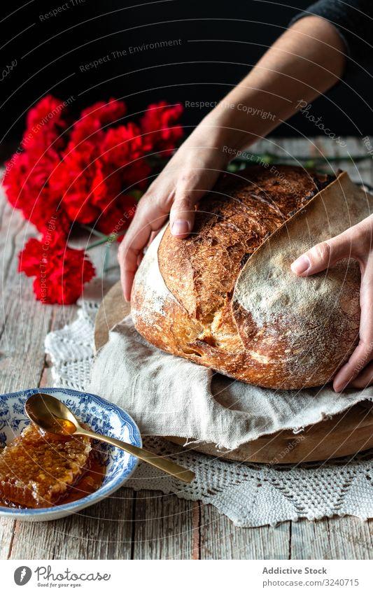 Erntehelfer, der Sauerteigbrot in die Nähe von Blumen und Honig legt Brot Liebling Person Tisch frisch Brotlaib Mahlzeit Lebensmittel Wabe gebacken rustikal