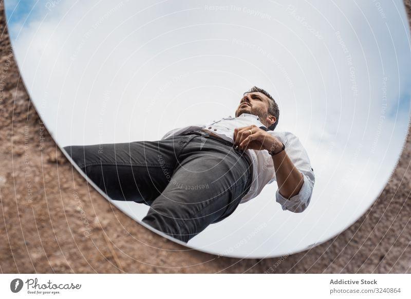 Ausgefallener Mann spiegelt sich im Spiegel am Boden Reflexion & Spiegelung ausgefallen verträumt weißes Hemd Hosenträger stehen Blauer Himmel gutaussehend Oval