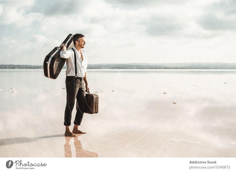 Fokussierter stilvoller Mann mit Koffer und Gitarren-Giggertasche am Meer stylisch Seeküste Gig-Tasche ernst Barfuß führen Wasser USA Ufer anstarrend
