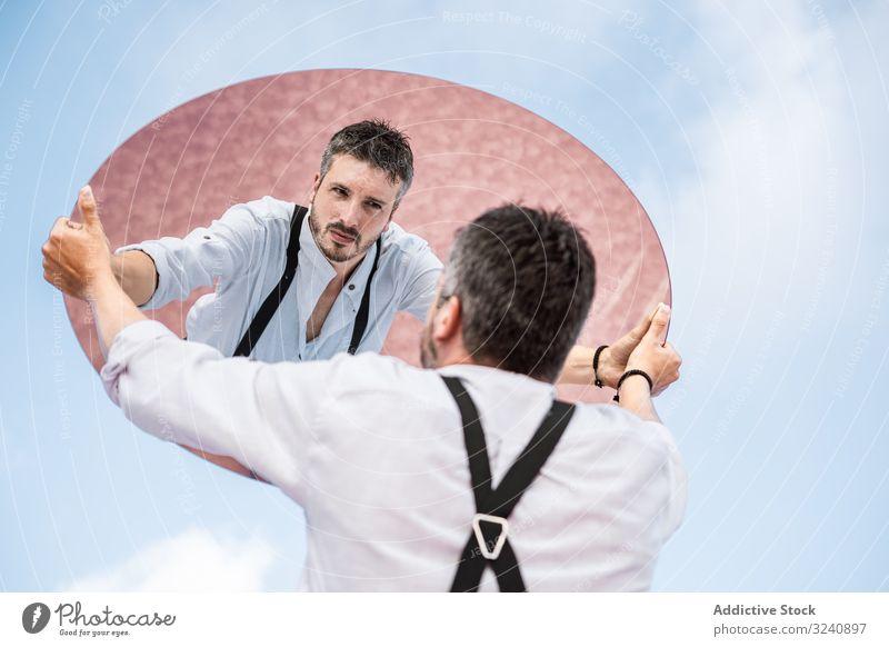 Stilvoller Mann hält Spiegel hoch und reflektiert Reflexion & Spiegelung stylisch besinnlich weißes Hemd Hosenträger stehen Blauer Himmel Heben tragen