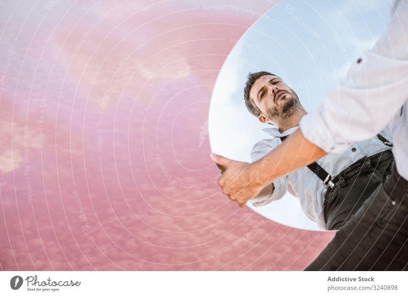 Stilvoller Mann hält Spiegel mit Reflexion Reflexion & Spiegelung stylisch besinnlich weißes Hemd Hosenträger stehen Blauer Himmel Heben tragen gutaussehend
