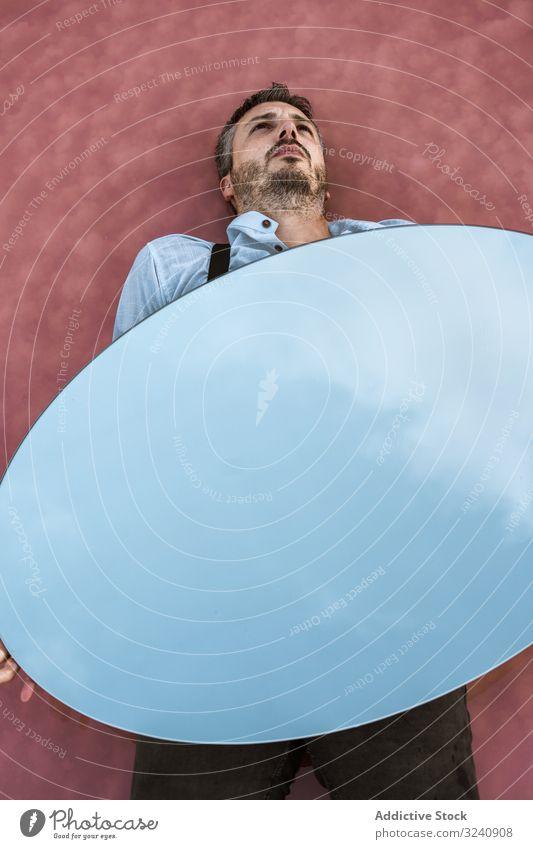 Liegender Mann hält Spiegel mit Reflexion Reflexion & Spiegelung liegend stylisch besinnlich weißes Hemd Hosenträger Blauer Himmel tragen gutaussehend Oval