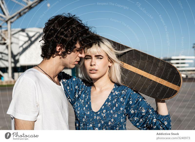 Trendy verliebtes Paar umarmt sich auf der Straße Umarmung Skateboard Liebe Umarmen amour Windstille Romantik Freund Freundin charmant romantisch spielend