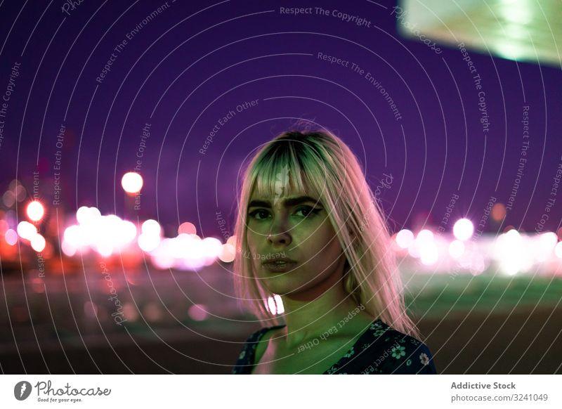 Großartige nachdenkliche erwachsene Frau schaut in der Dämmerung in die Kamera gegen den lebhaften Himmel Morgendämmerung Starrer Blick selbstbewusst