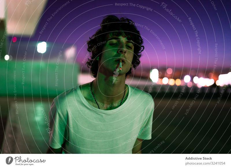 Erwachsener Mann raucht, während er bei Sonnenuntergang in die Kamera schaut Zigarette selbstbewusst Rauch Windstille Starrer Blick Interesse