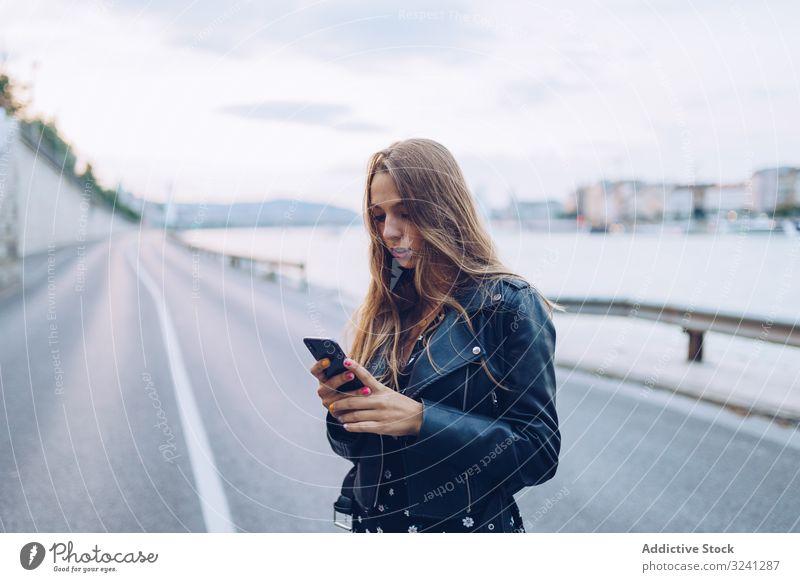 Langhaarige stylische Frau surft auf Smartphone Telefonanruf Großstadt ernst Nachrichten Straße klug Sprechen Empfang Budapest benutzend fokussiert Gespräch
