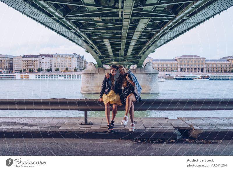 Lächelnde Freundinnen, die sich umarmen und auf dem Zaun entlang des Flusses unter der Brücke sitzen Frauen reisen Großstadt Tourist Architektur Spaß Urlaub