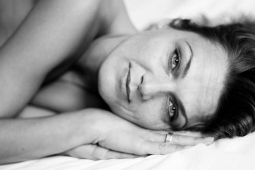 Im Liegen wirds schlimmer - homöopathisch betrachtet. Mensch feminin Frau Erwachsene Gesicht Arme Hand 1 30-45 Jahre brünett langhaarig Bett Ring Lächeln liegen