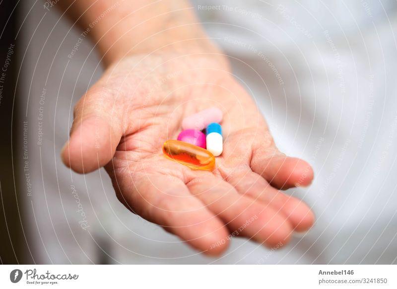 Viele mehrfarbige Pillen in den Händen eines Seniors. Schmerzhaftes Alter. Flasche Gesundheitswesen Behandlung Krankheit Medikament Krankenhaus Mensch Frau