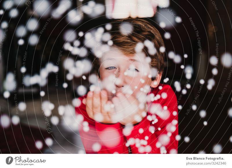 kleiner Junge, der zu Hause künstliche Schneeflocken bläst. Weihnachten Lifestyle Freude schön Spielen Winter Kind maskulin 1 Mensch 3-8 Jahre Kindheit Pullover