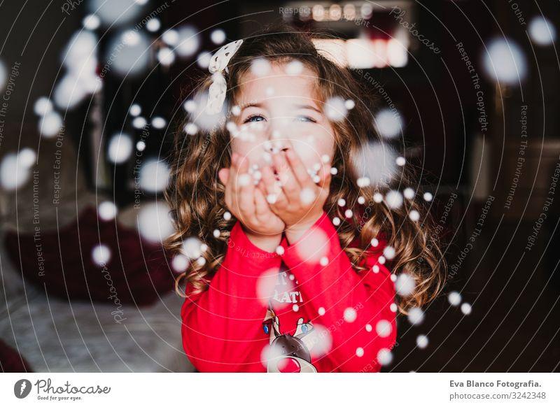 junges Mädchen, das zu Hause künstliche Schneeflocken bläst. Weihnachten Freude schön Spielen Winter Weihnachten & Advent Kind feminin Kleinkind 1 Mensch