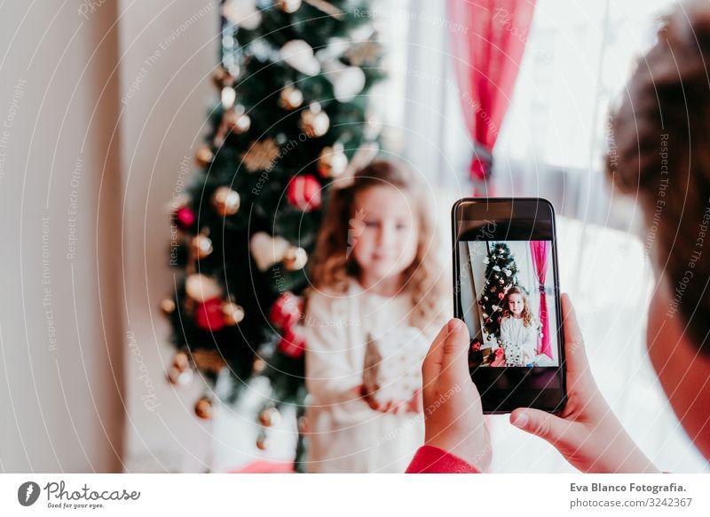 Bruder macht ein Foto von seiner Schwester mit dem Handy. Lifestyle Freude Spielen Winter Haus Weihnachten & Advent PDA Bildschirm Technik & Technologie Mensch