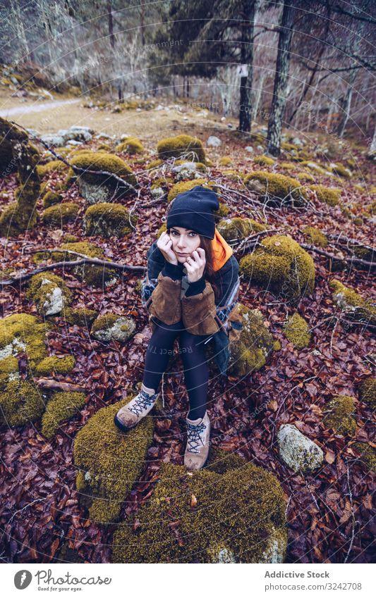 Gelangweilte Touristin ruht sich auf Felsen im Herbstwald aus ruhen Wald gelangweilt sitzen Stein Frau getrocknet Laubwerk braun Moos auf die Hand gestützt Hut