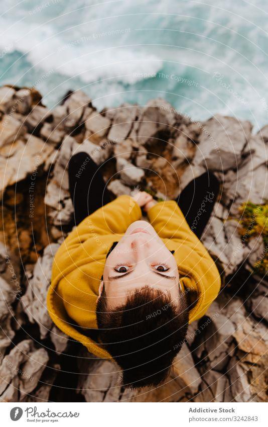 Frau in gelbem Kapuzenpulli an steiniger Küste Einsamkeit Ufer reisen winken Stein zuschauend träumen Harmonie Kontemplation einsam nachdenklich MEER Meer