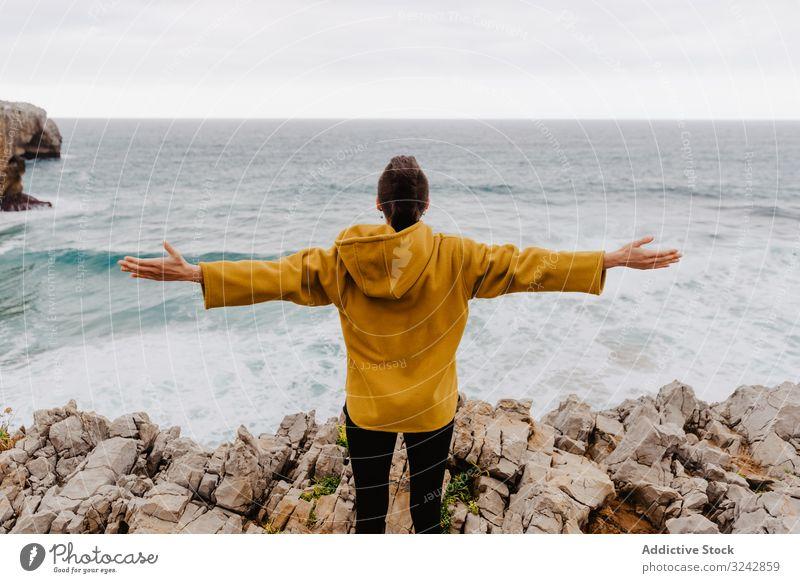 Person in gelbem Kapuzenpulli an steiniger Küste Einsamkeit Ufer reisen winken Stein zuschauend träumen Harmonie Stehen Kontemplation einsam nachdenklich MEER