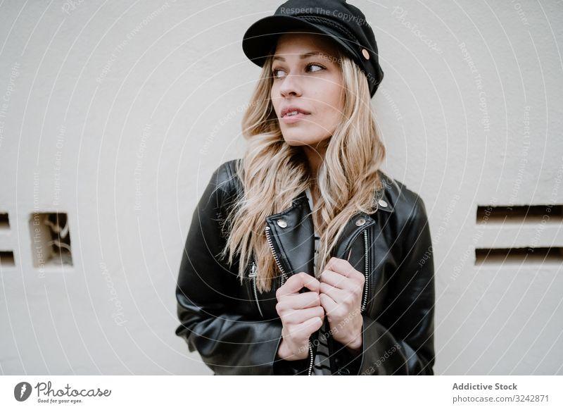 Stilsichere Frau geht auf der Straße stylisch cool urban trendy selbstbewusst Lederjacke provokant Jeansstoff lockig Lifestyle lässig langhaarig modern