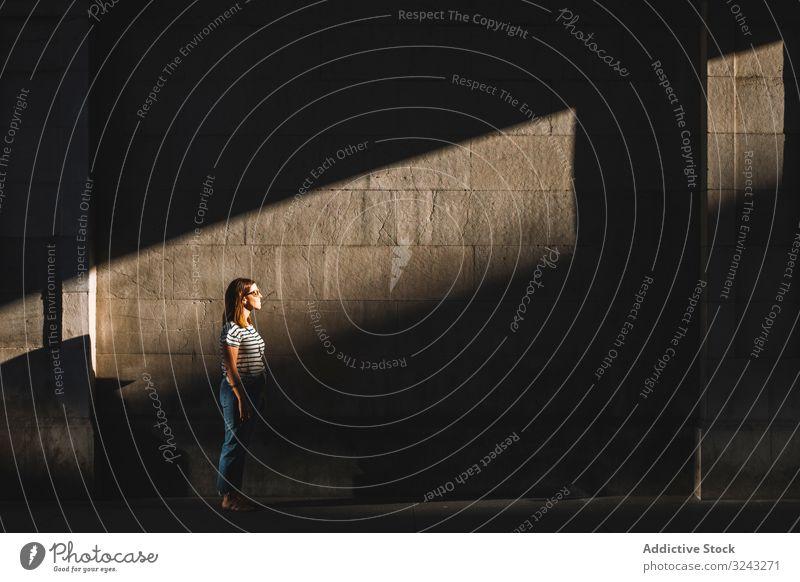 Frau steht im Sonnenlicht in dunkler Passage Schatten Wand dunkel Durchgang Großstadt Straße lässig Fleck ruhen sich[Akk] entspannen Sommer Stadt Gebäude