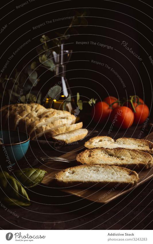 Toastet Zutaten auf dunklem Tisch Zuprosten Bestandteil Brot Basilikum Tomate Lebensmittel dunkel Mahlzeit frisch rustikal traditionell Abendessen Mittagessen