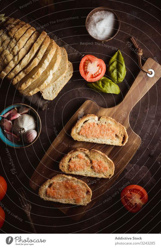 Gewürze und Gemüse in der Nähe von Toast Zuprosten Saucen Bestandteil Tomate Salz Knoblauch Basilikum Erdöl Brot Schneidebrett Tisch Lebensmittel Snack lecker