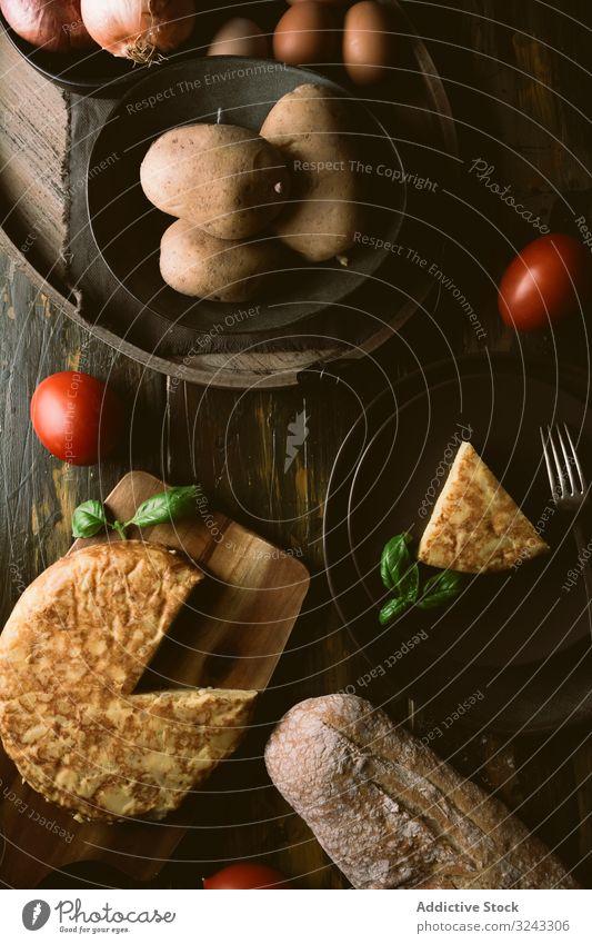 Kochzutaten rund um die Torte auf dem Tisch Pasteten Bestandteil Küche Tomate Ei Zwiebel Brot Kartoffel Lebensmittel Tortilla Basilikum rustikal Gebäck lecker