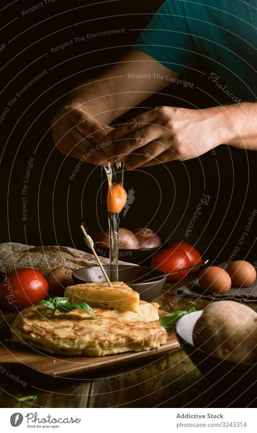 Erntehelfer bricht Ei in der Nähe von Kuchen Mann Pause Koch Bestandteil Pasteten Tortilla Lebensmittel Tisch rustikal dunkel Küche lecker geschmackvoll