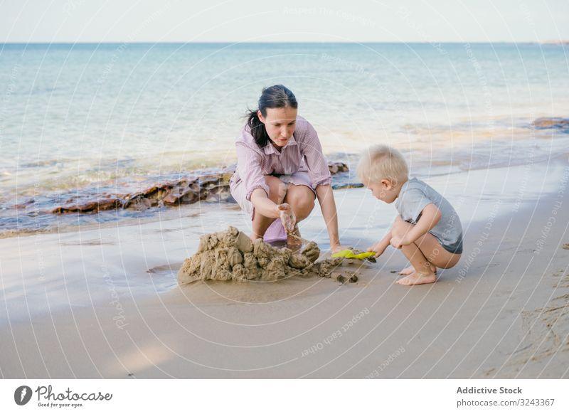 Kleinkind und Mutter spielen mit Sand am Strand gegen verschwommene Meereslandschaft bei Sonnenschein Kind tropisch Spiel MEER ruhen Urlaub Sohn Vorschule