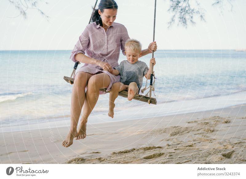 Fröhliches Kind schwingt mit der Mutter gegen verschwommene Meereslandschaft pendeln Strand sich[Akk] entspannen Zusammensein tropisch spielen besinnlich Sohn