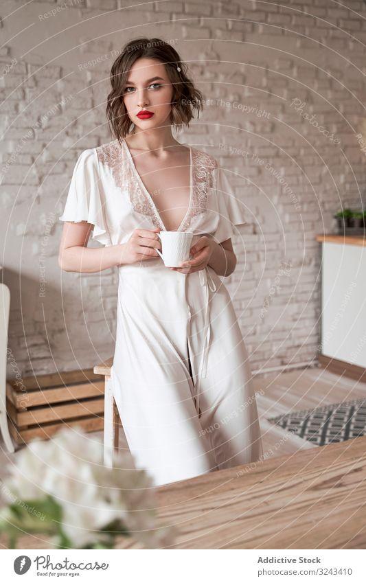 Nachdenkliche Frau, die bei einem heißen Getränk in der Küche wegschaut und nachdenklich ist besinnlich weißes Kleid hochzeitlich Kaffee Loft Angebot