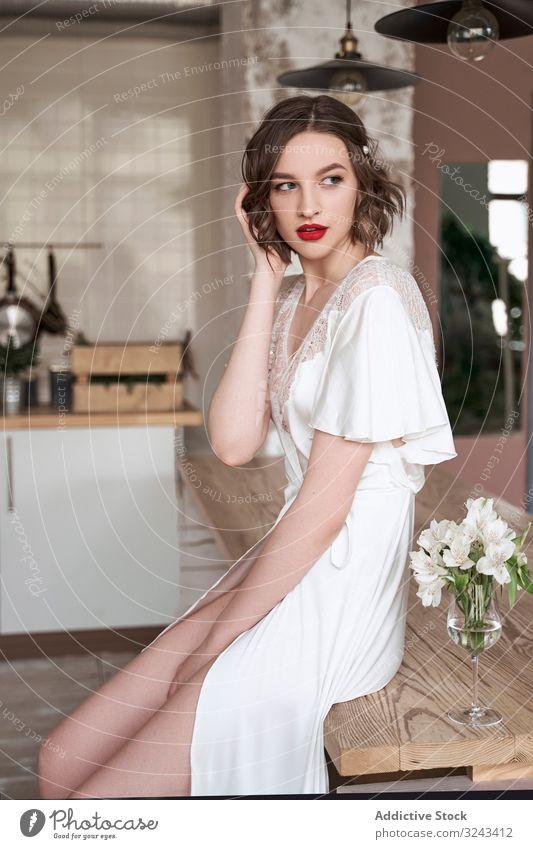 Attraktive, nachdenkliche junge Dame mit roten Lippen in weißem Kleid, die wegschaut und nachdenklich ist Frau Brautkleid sinnlich rote Lippen besinnlich schick
