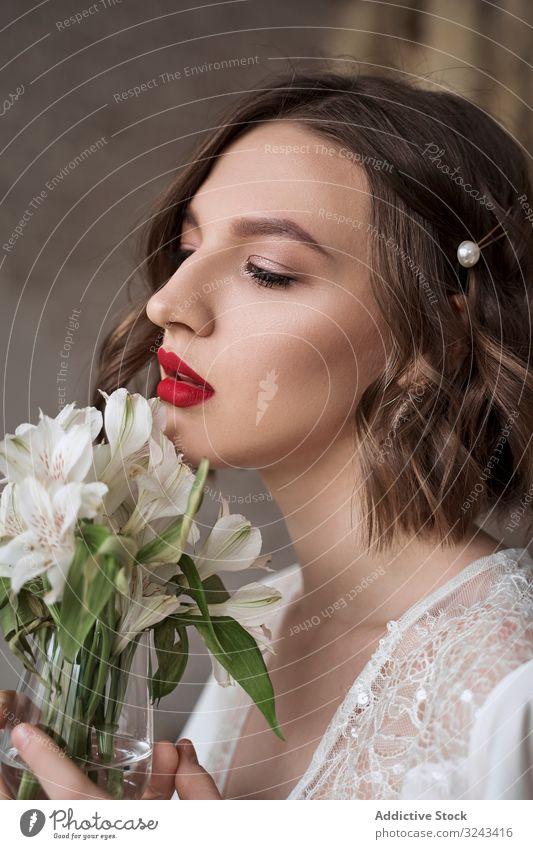 Sinnliche Frau mit roten Lippen, die weiße Blumen hält und träumt weißes Kleid Brautkleid sinnlich sanft rote Lippen Make-up träumen Charme Angebot Schönheit