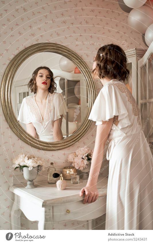Attraktive ernsthafte junge Frau, die im Boudoir steht und in einen großen runden Spiegel schaut Reflexion & Spiegelung sinnlich Verlockung Brautkleid