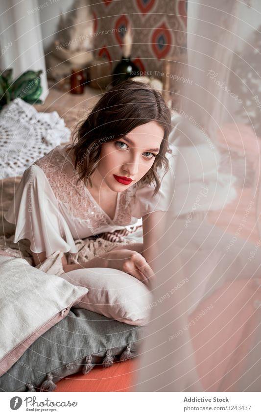 Wunderschöne Frau mit roten Lippen in weißem Kleid, die in die Kamera schaut, während sie auf dem Boden neben dem Sofa sitzt Brautkleid rote Lippen altehrwürdig