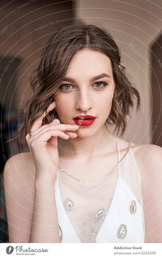 Wunderschöne junge selbstbewusste Frau mit roten Lippen, die in die Kamera schaut weißes Kleid trendy sinnlich Windstille Make-up rote Lippen besinnlich Charme