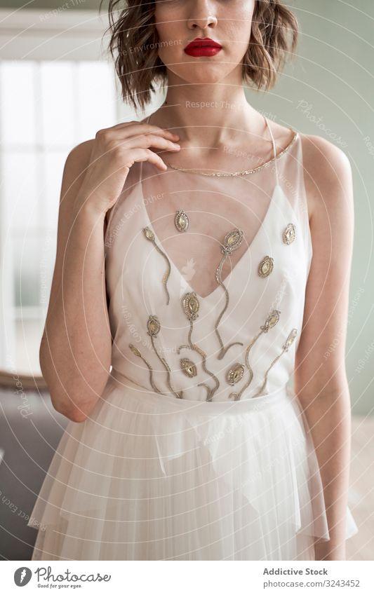 Junge Dame mit roten Lippen in elegantem weißen Kleid, die in die Kamera schaut Frau Brautkleid trendy schick Starrer Blick rote Lippen traumhaft Make-up