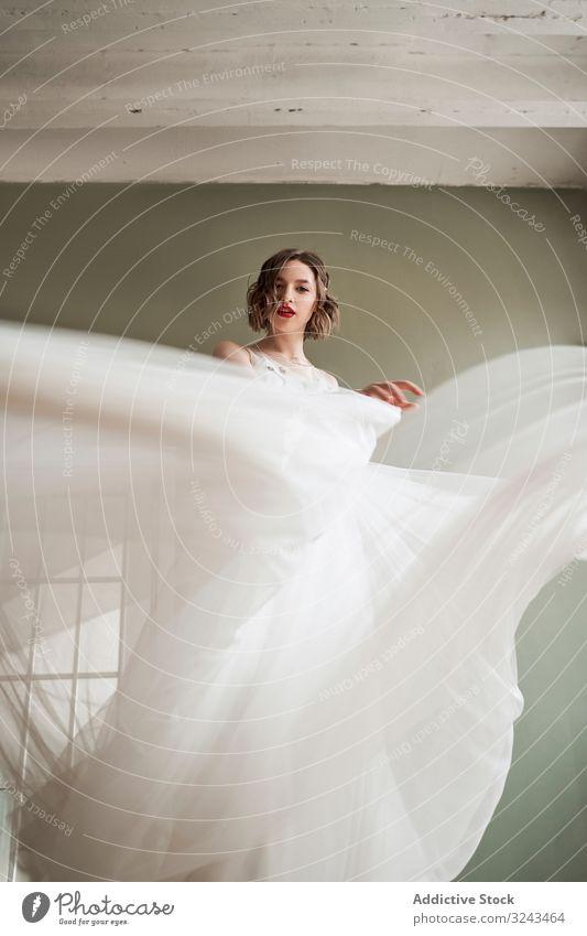 Attraktive, heitere junge Frau in weißem Kleid tanzt und schaut in die Kamera Brautkleid fließen Angebot durchsichtig schlanke sanft rote Lippen