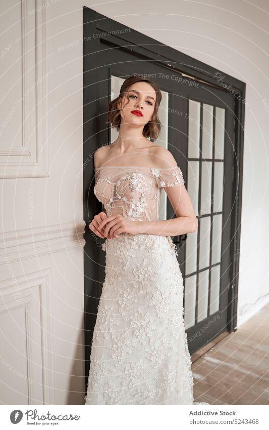 Prächtige nachdenkliche junge Braut in weißem Spitzenkleid schaut in die Kamera und grübelt Frau Brautkleid Mode rote Lippen elegant träumen romantisch schick