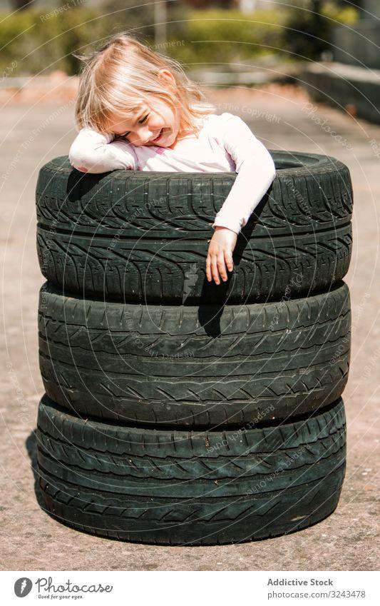 Kleines Mädchen ruht in Reifenstapel Kind unanständig Spaß spielen Streich Stapel wenig Glück Freude Kindheit aktiv heiter Freizeit Lächeln Lachen Spiel