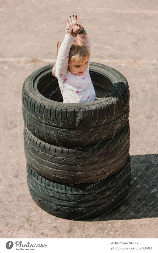 Kleines Mädchen im Reifenstapel stehend Kind unanständig Spaß spielen Streich Stapel wenig Glück Freude Kindheit aktiv heiter Freizeit Lächeln Lachen Spiel