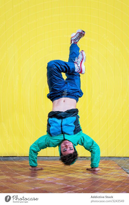 Geschickter Breakdancer beim Handstand in der Bewegung cool stylisch Kultur Streetstyle Lifestyle Hip-Hop flippig Stil Freestyle Spaß Leistung Teenager männlich