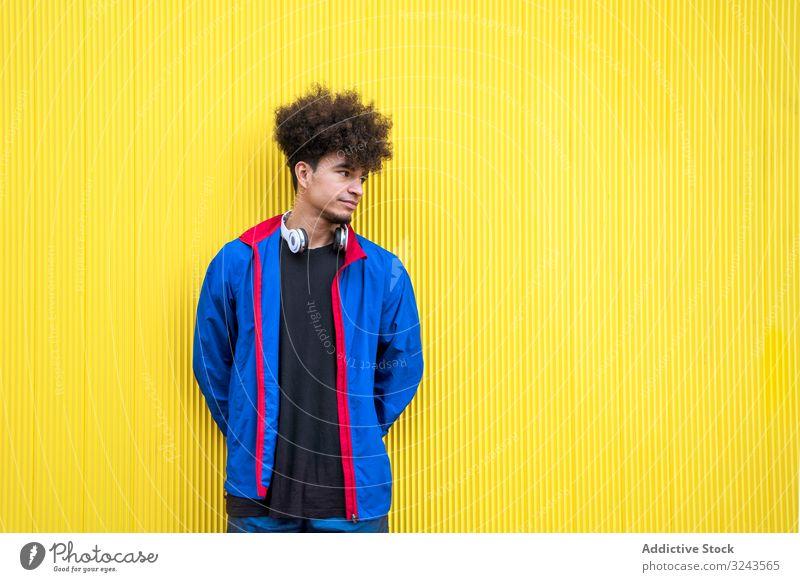 Stylischer ethnischer Hipster im Streetstyle-Outfit an gelber Wand Straße stylisch tausendjährig Kopfhörer Musik Stil lebhaft pulsierend träumen Generation jung