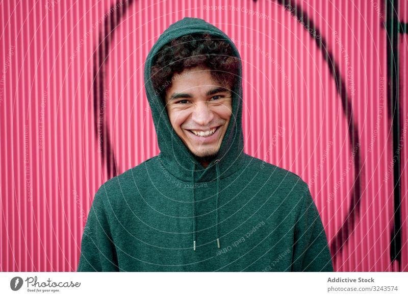 Junger ethnischer Hipster in Kapuzenpullover an Straßenmauer mit Graffiti Mann Streetstyle cool lebhaft urban Kapuzenpulli Großstadt Kultur Stil Generation