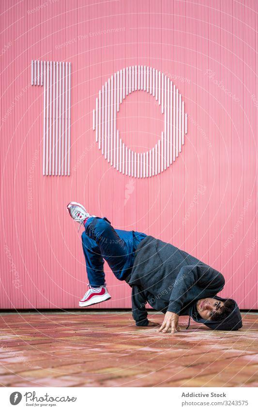 Junger männlicher Teenager beim Breakdance auf der Straße cool Sport Tanzen Hip-Hop Stil Bewegung Mode jung urban Spaß Zeitgenosse Musik Aktion Kultur Freestyle