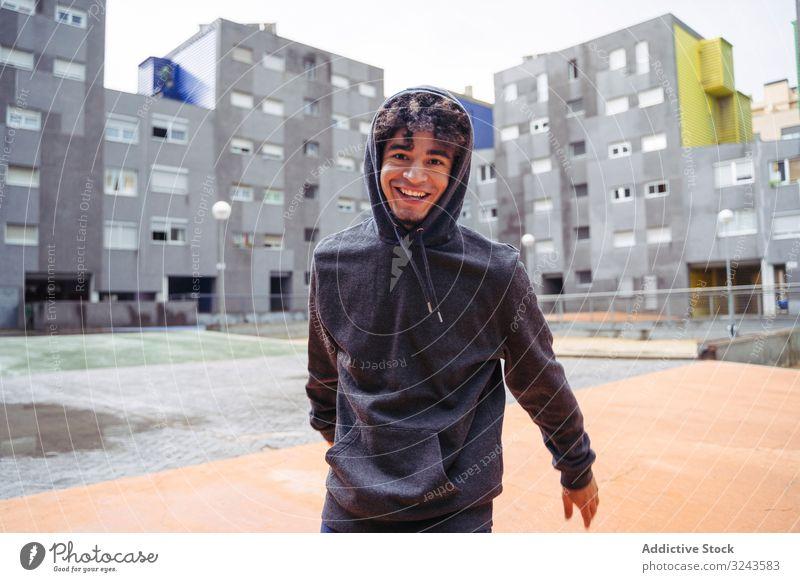 Wehmütiger Mann in legerer Kleidung im Hof Kapuzenpulli Straße Großstadt kalt jung ethnisch Kapuze auf Lifestyle Hipster stylisch nachdenklich modisch Jugend