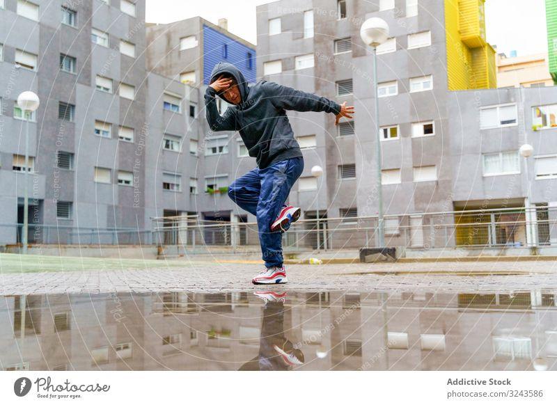 Hipster in Freizeitkleidung beim Breakdance auf der Straße Mann urban Kultur flippig Sport Tanzen Hip-Hop Stil Bewegung Mode jung Musik Hof regnerisch Aktion