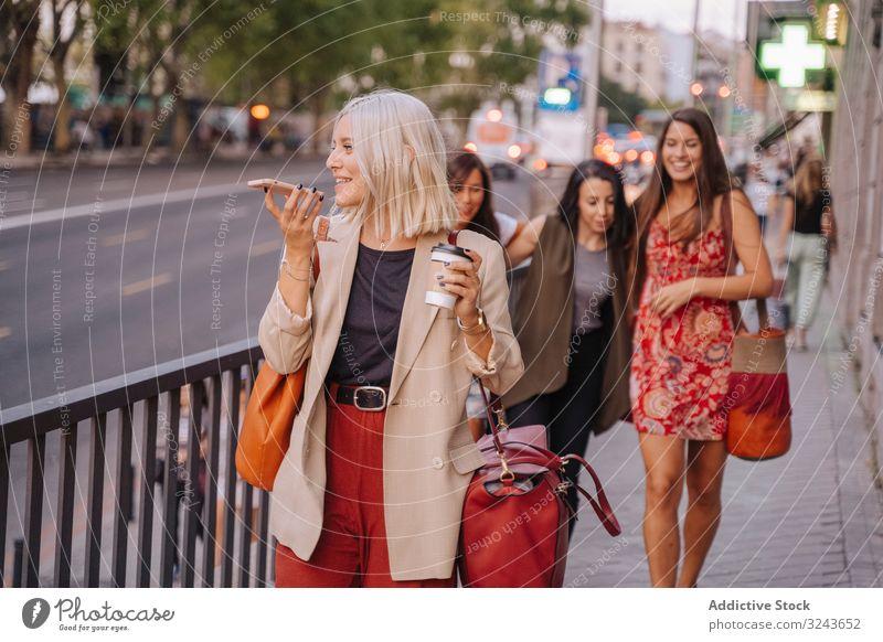 Fröhliche Frau nimmt Audiobotschaft auf und geht auf der Straße Smartphone Aufzeichnen Spaziergang Lächeln benutzend trinken Imbissbude stylisch Großstadt