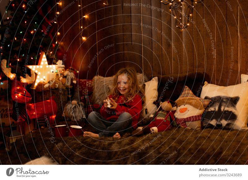 Kleines Mädchen mit Teddy umgeben von Weihnachtsschmuck Kind dekorierend Weihnachten Baum Feier Dekoration & Verzierung heimwärts Feiertag Kindheit Winter