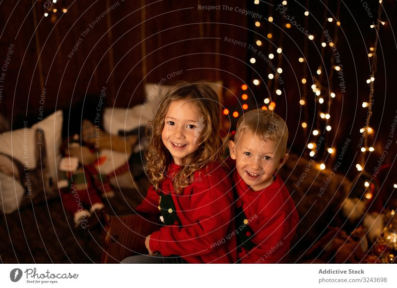 Geschwister sitzen zu Weihnachten auf einer hölzernen Pferdeschaukel Kind dekorierend Baum Feier Dekoration & Verzierung heimwärts Mädchen Kindheit Saison